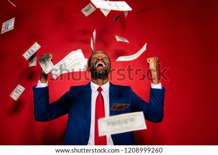 Emotion reaction concept. Crazy man in stylish trendy style formal wear tux tuxedo jacket suit tie close eyes raised fists up isolated on red bright background under money rain #1208999260