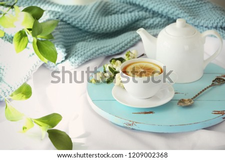 Wooden board with cup of lemon tea and teapot on fabric #1209002368