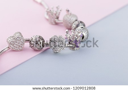 Bracelet with silver charm beads with gems. Flower, crown, ball, heart beads.  Product concept for jeweler Royalty-Free Stock Photo #1209012808