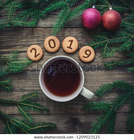 Tinted Christmas picture with 2019 new year on cookies, fir branches, toys, warm scarf and a mug of hot tea on a wooden background