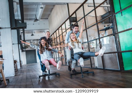 cheerful young colleagues having fun together at workspace   #1209039919