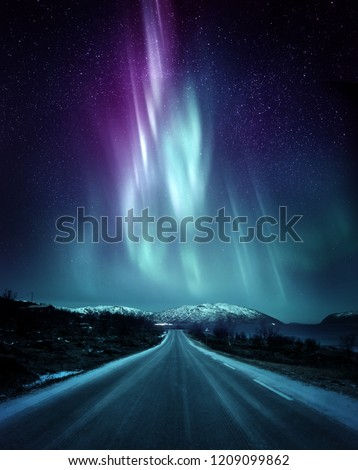 A quite road in Norway with a spectacular Northern Light Aurora display lighting up the night sky above the mountains. A popular destination within the arctic circle for hunting the Northern Lights.  #1209099862