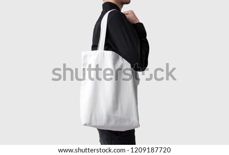 Man is holding bag canvas fabric for mockup blank template isolated on gray background.  #1209187720