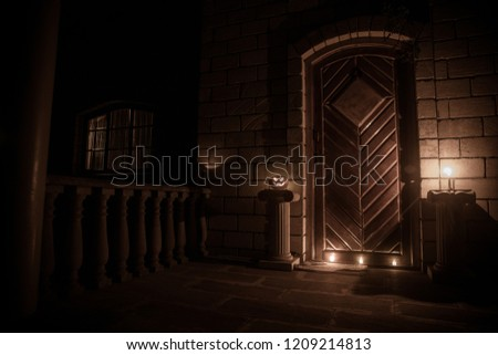 Front door to a house decorated with Halloween pumpkin. Halloween pumpkin on a door steep at night