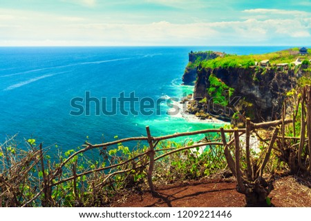 Azure beach with rocky mountains and clear water of Indian ocean at sunny day / A view of a cliff in Bali Indonesia / Bali, Indonesia #1209221446