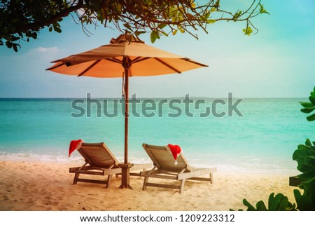 Christmas on beach -chair lounges with Santa hats at sea #1209223312