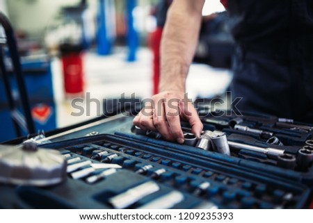 Set of tools for repair in car service - mechanic's hands, close up #1209235393