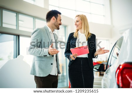 Portrait of young saleswoman in car dealership #1209235615