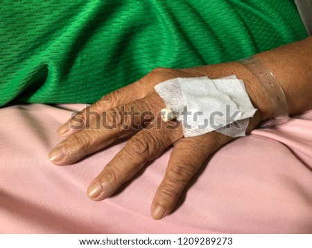 Hand of elderly has bandage cover and has syringe intravenous under the bandage. Patient in emergency room at hospital, due to illness or accident, treatments care, First Aid. Selective focus. #1209289273