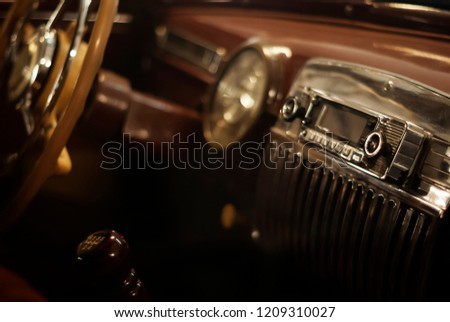 Blurred warm background - a fragment of the interior of a vintage car, focus on the handle of the radio #1209310027