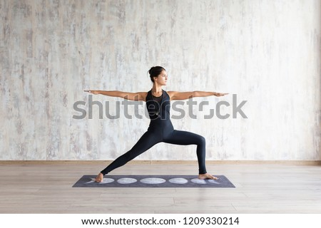 Slender asian girl standing in yoga asana on mat against concrete wall. Peaceful focused girl standing in Warrior Two exercise, Virabhadrasana pose, wearing black sportswear. No stress concept. #1209330214