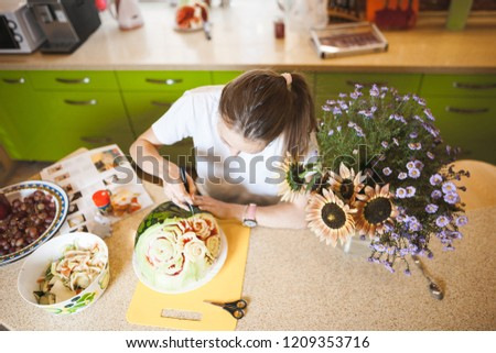 A young girl carving watermelon in her beautiful kitchen. Photo hobby #1209353716