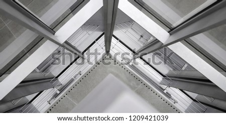 Fragment of office building interior featuring corner of structural glazing. Hi-tech architecture made of steel / aluminum and glass. Material background on the subject of construction industry. Royalty-Free Stock Photo #1209421039