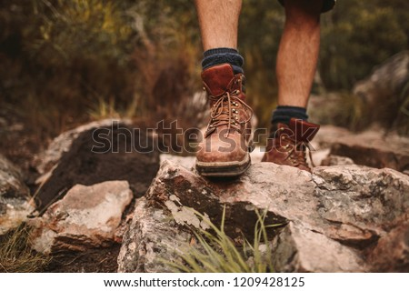 Closeup of male hikers shoes on rocky trail. Man walking through rugged path wearing trekking boots. Royalty-Free Stock Photo #1209428125