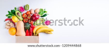 Healthy food in paper bag fruits and vegetables on white. Concept healthy food background. Vegetarian food. Shopping food supermarket. Long web format #1209444868