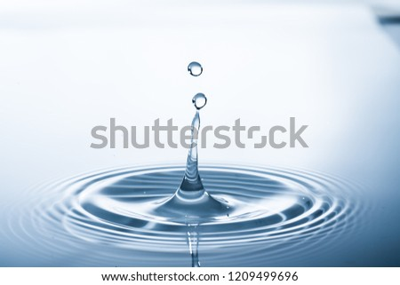 Water drop falling into water making a perfect droplet splash #1209499696