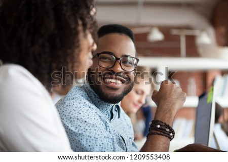 Close up of smiling African American employee look at female colleague chatting in office, happy black male worker talk with woman coworker, having casual conversation at workplace, have fun Royalty-Free Stock Photo #1209553408
