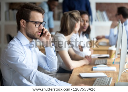 Serious male worker talk on phone consulting client in office, focused millennial employee speak on cell while working at computer in coworking workplace, man solving business problems online Royalty-Free Stock Photo #1209553426