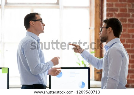 Mad male colleagues have disagreement in office arguing on work issues, furious millennial employee point at coworker blaming for mistake or failure, businessman accuse partner disputing at workplace #1209560713
