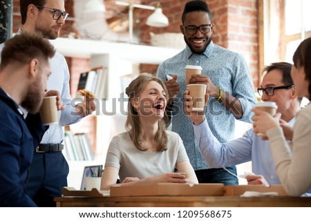 Happy diverse colleagues have fun at lunch break in office, smiling multiracial employees laugh and talk eating pizza and drinking coffee, excited workers celebrate shared win ordering takeaway food #1209568675