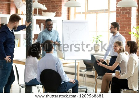 Smiling African American mentor or coach make flipchart presentation for diverse employees, excited black presenter present project on whiteboard, coworkers laugh having fun at casual briefing #1209568681
