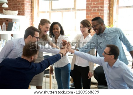 Excited multiracial colleagues give high five involved in teambuilding activity at meeting, happy diverse workers join hands celebrate success or win, show team spirit and unity. Cooperation concept #1209568699