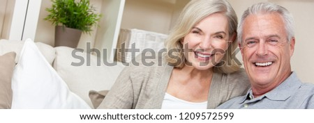Web banner panoramic image of happy senior man and woman couple sitting together at home smiling and happy with perfect teeth Royalty-Free Stock Photo #1209572599