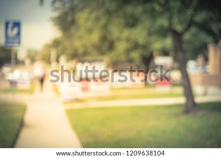 Vintage tone blurred row of yard signs at residential street for primary election day in Dallas county, Texas, US. Signs greeting early voters, political party posters for the midterm election concept