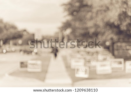 Vintage tone motion blurred people walking on residential street near yard sign at for primary election day in Dallas, Texas, USA. Signs greeting early voters.