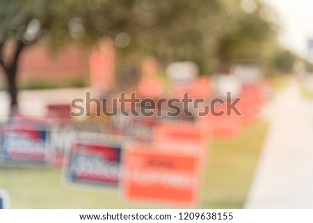 Blurred image row of yard sign at residential street for primary election day in Dallas county, Texas, USA. Signs greeting early voters, political party posters for the midterm election concept