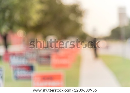 Motion blurred people walking on residential street near yard sign at for primary election day in Dallas, Texas, USA. Signs greeting early voters.
