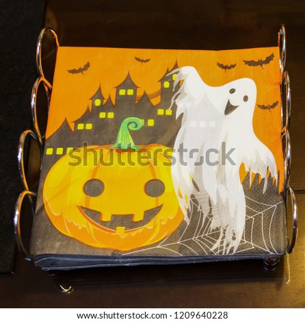 Halloween decoration. Halloween decoration paper napkins with picture of pumpkin and a ghost, on a orange color background.