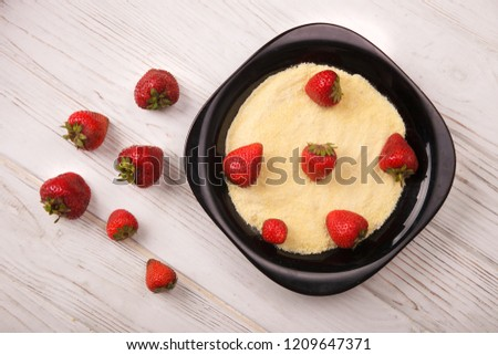 Healthy breakfast: corn porridge and strawberry in black plate. Strawberry scattered around on light wood background. Top view. Flat lay.  #1209647371