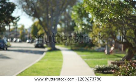 Quiet street scene of the sidewalk and idyllic homes in a suburban neighborhood #1209673780