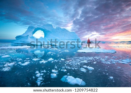 Little red sailboat cruising among floating icebergs in Disko Bay glacier during midnight sun season of polar summer. Ilulissat, Greenland. #1209754822