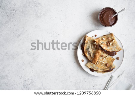 Crepes with chocolate and hazelnuts. Homemade thin crepes for breakfast or dessert on white, copy space. Royalty-Free Stock Photo #1209756850