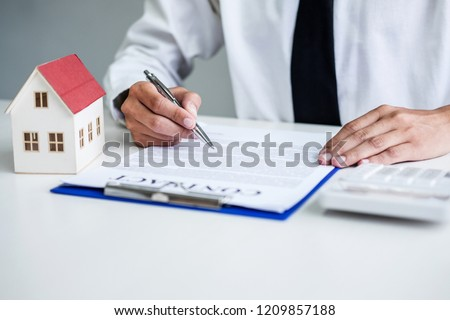 Man sign a home insurance policy on home loans, Businessman signing contract insurance. #1209857188