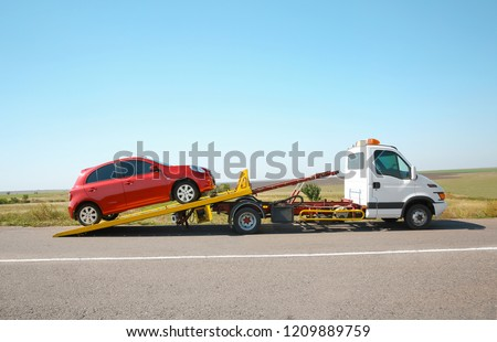 Tow truck with broken car on country road #1209889759