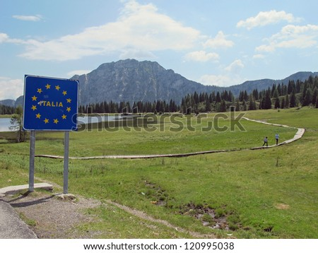 blue sign with yellow stars on the Italian border