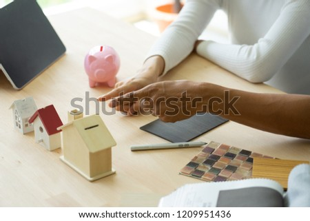 Happy couple plan buying house.Concept for Couple saving money for buy home and real estate. Select material for decorate furniture. #1209951436