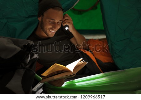 Young man in sleeping bag reading book with flashlight inside of tent Royalty-Free Stock Photo #1209966517