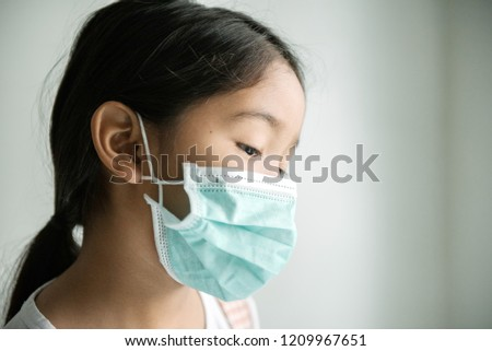 Portrait of preschooler little cute asian kid sick girl, cough wearing protective mask. #1209967651