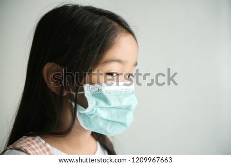Portrait of preschooler little cute asian kid sick girl, cough wearing protective mask. #1209967663