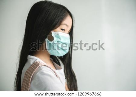 Portrait of preschooler little cute asian kid sick girl, cough wearing protective mask. #1209967666