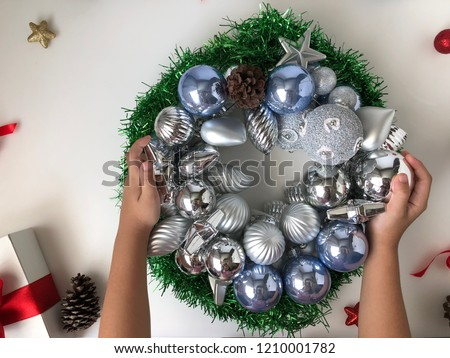 Put the silver ball into a Christmas wreath placed on a white table #1210001782
