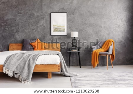 Grey and orange accents in simple and elegant bedroom with king size bed and painting on the empty concrete wall, real photo #1210029238