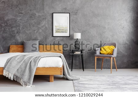 Grey blanket and pillow on the wooden bed with white bedding in stylish bedroom interior with concrete wall #1210029244