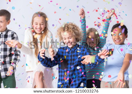 Happy boy have fun during birthday party with smiling friends with confetti #1210033276