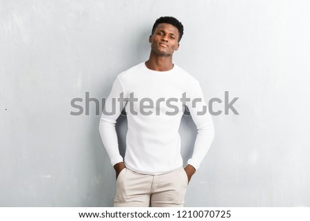 Young afro american man posing on textured grey wall #1210070725