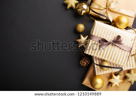 Beautiful christmas golden silver deco baubles with gifts on dark black background. Flat lay design. Copy Space. Horizontal. #1210149889